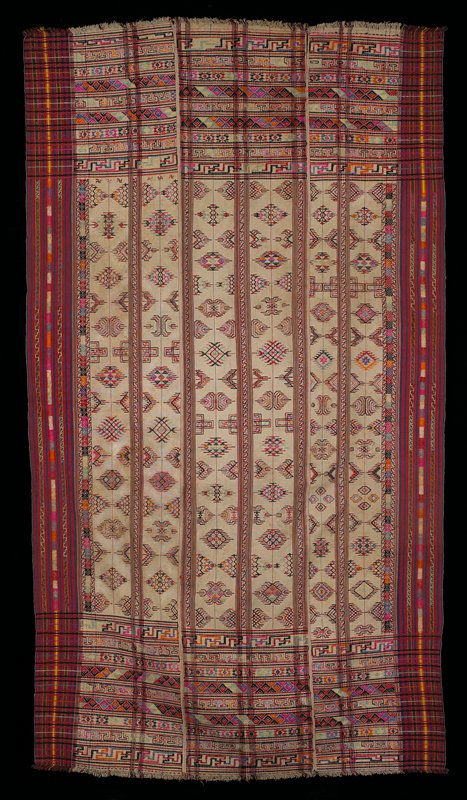 Three panels sewn together; natural cotton background with multicolored embroidery; warp stripe border in red, blue, green, yellow.