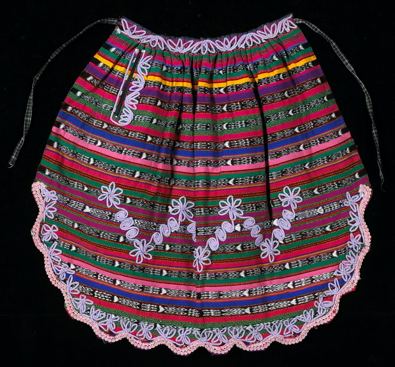 Multi-colored apron made from ikat material; one pocket with zipper and two decorative ribbons; edge is cut in scalloes and waist is pleated with two woven ties; pink edging follows scalloped hem; purple cording forms decorative patters along edges, pocket openings and center panel.