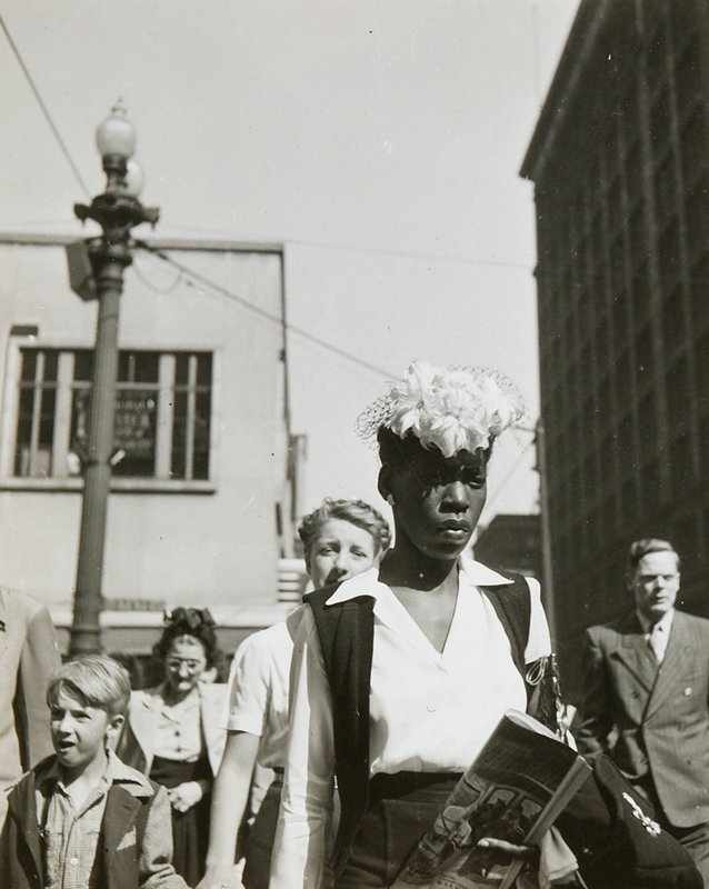 black woman wearing a white flowered hat, white blouse and dark vest; man in suit at right; woman holding little boy's hand behind black woman; another woman in background