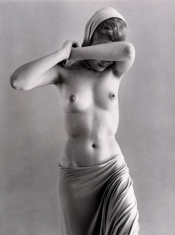 standing woman nude from waist up; drape wrapped around hips; arms up with PL over face; scarf on head; white mat