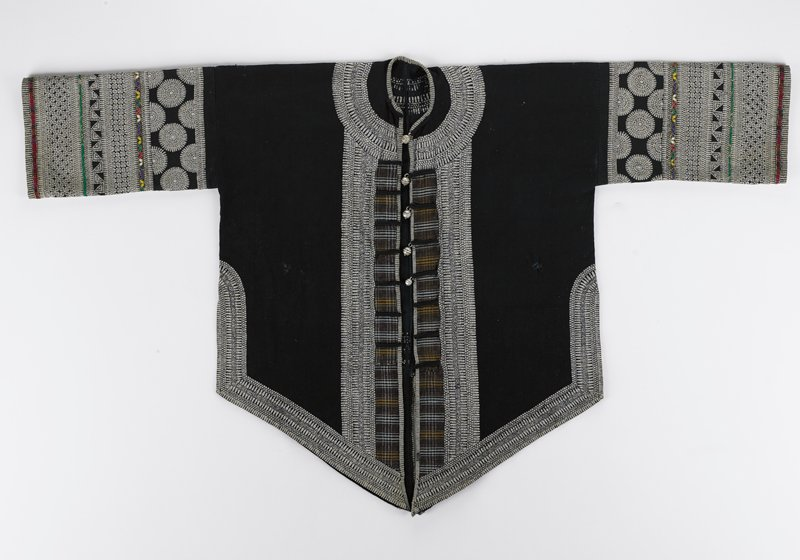 black ground; sleeves have floral/ rondel design; repeating geometric borders; brown plaid at front opening; five bell-like metal buttons; applique trim with gold threads