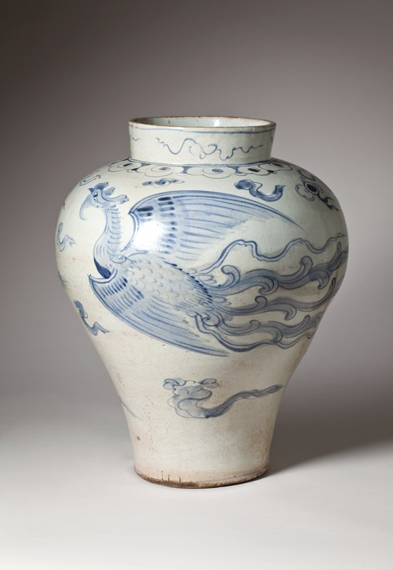white jar with very narrow base and wide shoulder; two phoenixes among stylized clouds and flames rendered in blue; slightly irregular shape
