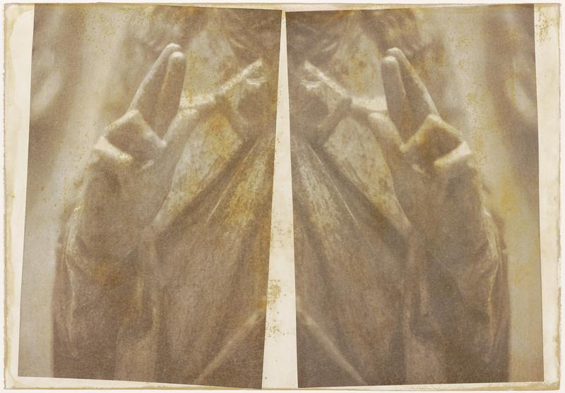 two mirror images of hands in blessing gesture (two fingers raised) with drapery in background; sheet treated to show premature yellowing and foxing
