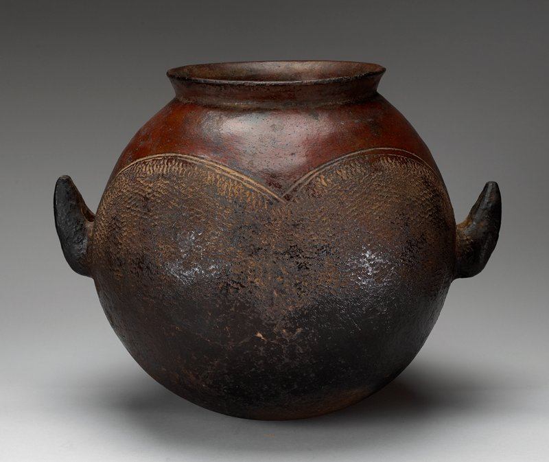 round bodied container; wide mouth, slightly flaring outward; pair of thick, upward-pointing handles; curved lines separating reddish top of pot from texturized darker bottom