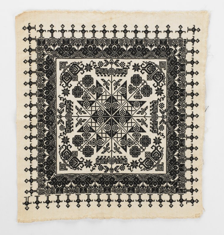 off-white fabric with cross-stitch pattern in black overall; central square with star and flower designs; geometric border with figures at edges