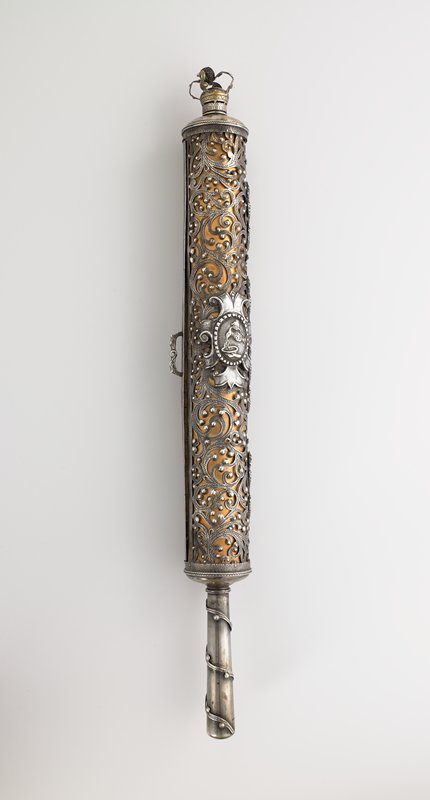 tube with openwork design with applied grapes, candelabra, 2 tablets and plaque with liquid being poured from a pitcher into a basin, backed with copper; open crown at top; handle with twining applied vine