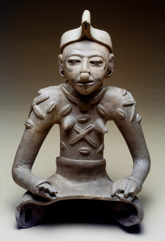 Seated female figure, legs missing, wearing a short apron-like garment terminating at the knees. Upper body clothed in a laced jerkin suggested by applied rolls of clay. Wide bands of clay form a turban headdress and wristlets. A thick roll of clay with ball pendant makes the necklace and a ball of clay serves as a nose ornament. There are traces of painted bands around the eye sockets, and around the slit mouth. Ear plugs and rings. The hands, resting on knees, are sketchily modeled. Restored at neck.