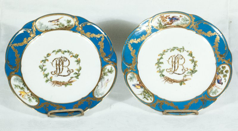 dinner plate, border in turquoise blue decorated with swags of gold leaves joining three oval medallions reserved in white and painted with landscapes and birds, scene differing from plate 44.42.1; in the center of the plate the monogram of a member of the Rohan family in gold within a wreath of gold leaves and acorns emerging from a tree stump; underglaze stone grey; the pieces in this group are part of a set made for the Rohan family during the reign of Louis XV