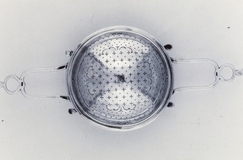 punch strainer with double scrolled handles and bowl pierced in a design of circles and narrow crosses