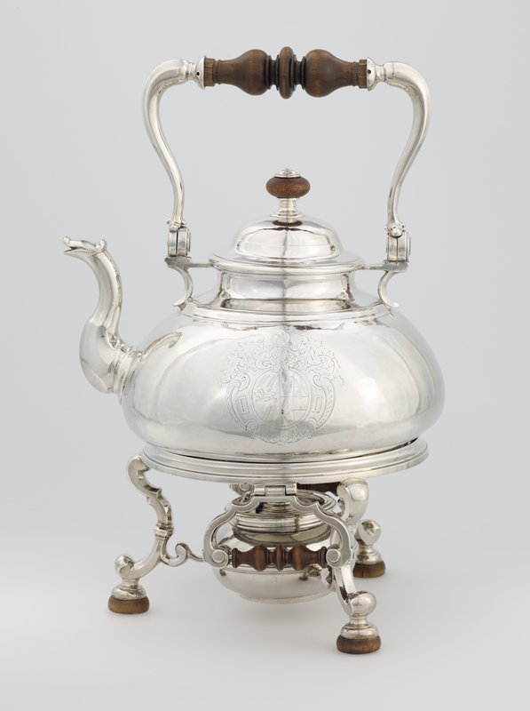 pear-shaped kettle in characteristic Queen Anne style flat base, duck-necked spout, swing handle with wood grip,attached to body with brackets; domed lid; body engraved with Arms of Morris of Cardigan, Wales; tripod stand with moulded ring on three scrolled legs to which are attached the brackets supporting spirit lamp; two hinged handles on stand; object numbered .1-4.