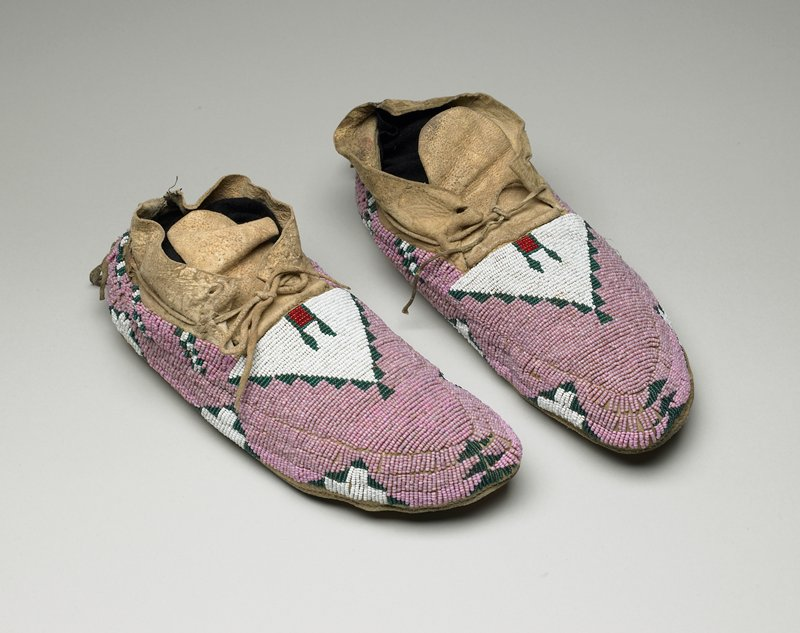 beaded uppers; primarily pink, with white triangle design with green and red interior, surrounded by green designs on top; white and green designs along edges; rawhide bottoms, around foot opening, tongues, ties, and tassels at back