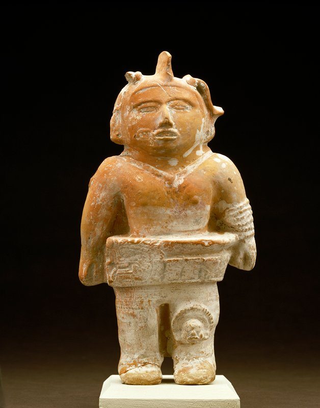 figure wears a replica of a heavy stone yoke at waist over skirt with fret motif; necklace; bands of bracelets on left arm; headdress broken at right. On the left knee a nead with round headdress in relief. Hole in right shoulder forms hook from which rattle could be suspended. The mould for front of body is well designed but assembled crudely with the mould for back.; Pinkish white pottery