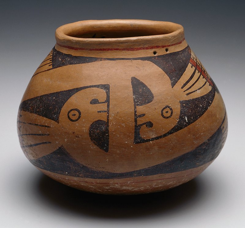 olla, black on terra cotta, with a design of rayed fish heads with bodies circling the jar in a bold scroll pattern; narrow lines of red at neck and base, together with red squares in the fish rays, put this in Ramos polychrome group; the rim has double piercing for carrying cords; 'Casas Grandes' type, Tardio phase