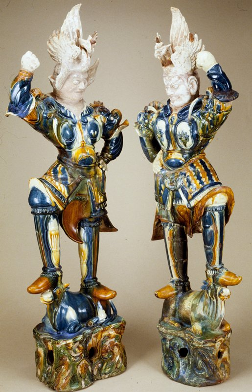Guardian of one of the quarters of the Buddhist heaven. ca 725 A.D. Glazed pottery tomb figure, one of a pair, wearing armor and standing on a kneeling bull. The costume is predominantly blue in tone, but there is much use of mottled yellow, brown and blue in the skirt sections. Elements of Sassanian design in armor. Head and phoenix headdress unglazed.