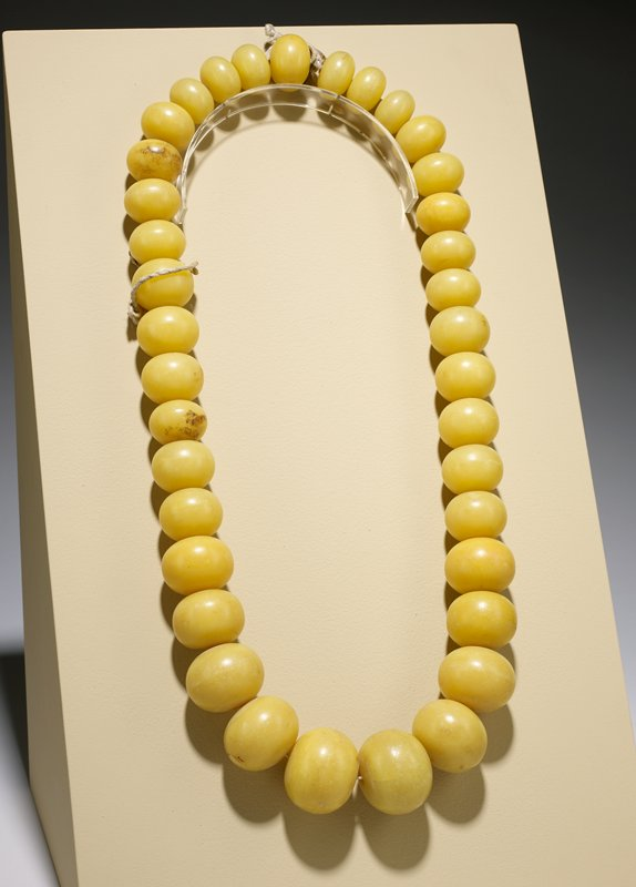 graduated opaque yellow beads strung together; two sections separated by braided cotton thread
