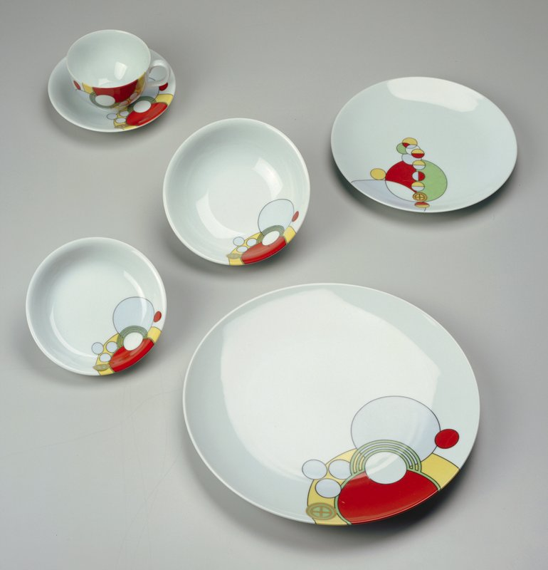 consists of 6 complete place settings, each composed of 7 pieces (cup, saucer, dinner plate, salad plate, bread plate, cereal bowl, fruit bowl); white background with circular motif design in blue, red, yellow and green with black or gold outlines; designed for the Imperial Hotel, Tokyo