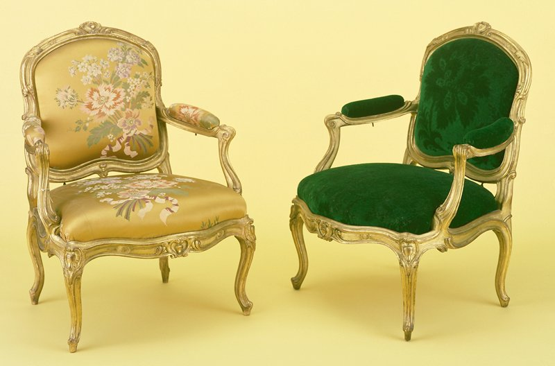 Set of Eight Louis XV Fauteuils, giltwood with detachable cartouche-shaped backs, upholstered arm-rests and serpentine drop-in seats. Backs with broad molded frames edged with scrolls interrupted by foliate sprays and centered by cabochon and cartouche crestings with outscrolled arm-supports, waved seat-rails of undulating outline centered by trefoil cabochon cartouche clasps on molded cabriole legs headed by similar clasps. four stamped I. Lebas. Six are coveredin polychrome gilt ground floral brocade and two are covered in dark green floral patterned velvet.