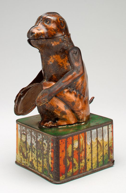 bronze-brown monkey sits with tray in both hands on a rectangular box; stopper to bank slides off base