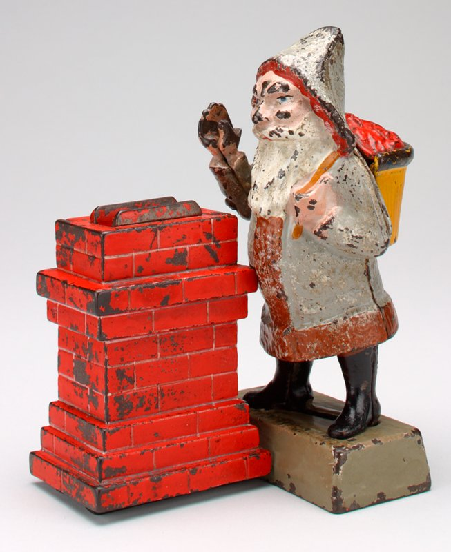 Santa Claus in light grey and brown coat holds yellow and red bag over left shoulder; Santa stands on rectangular stand; red rectangular chimney on his PR side below right hand