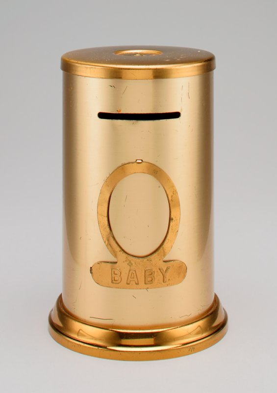 "cylindrical form; gold metal; plate on front printed ""BABY"""