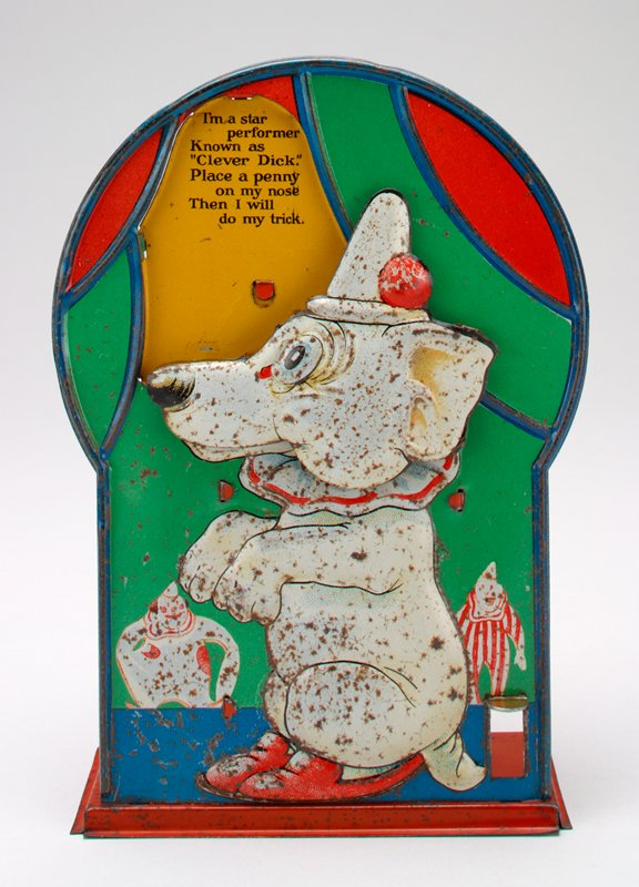 front relief panel of white dog wearing hat, ruffled collar and shoes, with 2 clowns in background; red box and platform on back