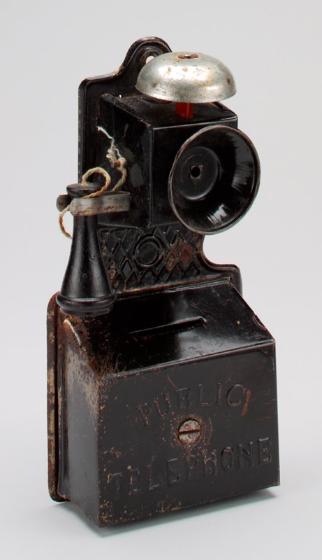 black metal wall phone; silver metal bell at top; black wooden earpiece connected with string; silver metal crank handle