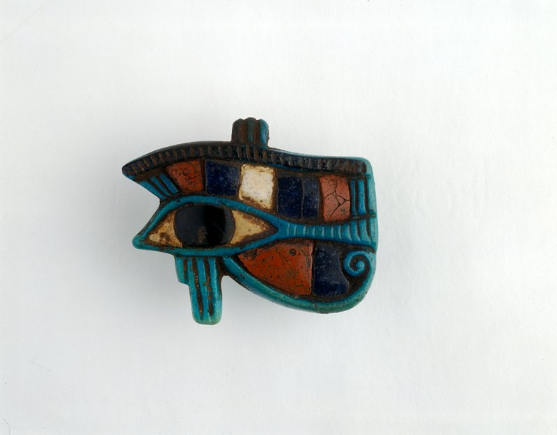 Horus eye green; elaborate detail and mosaic work; two rings on edge for suspension; a beautiful piece of work - finer detail than in 279; alabaster and red jasper, at least, the real stone and not glass imitation some inlays fallen out; lavender glass below eye Udjat: Eye of Horus (Eye of Ra); green faience with red jasper and alabaster with lavendar glass inlay beneath eye
