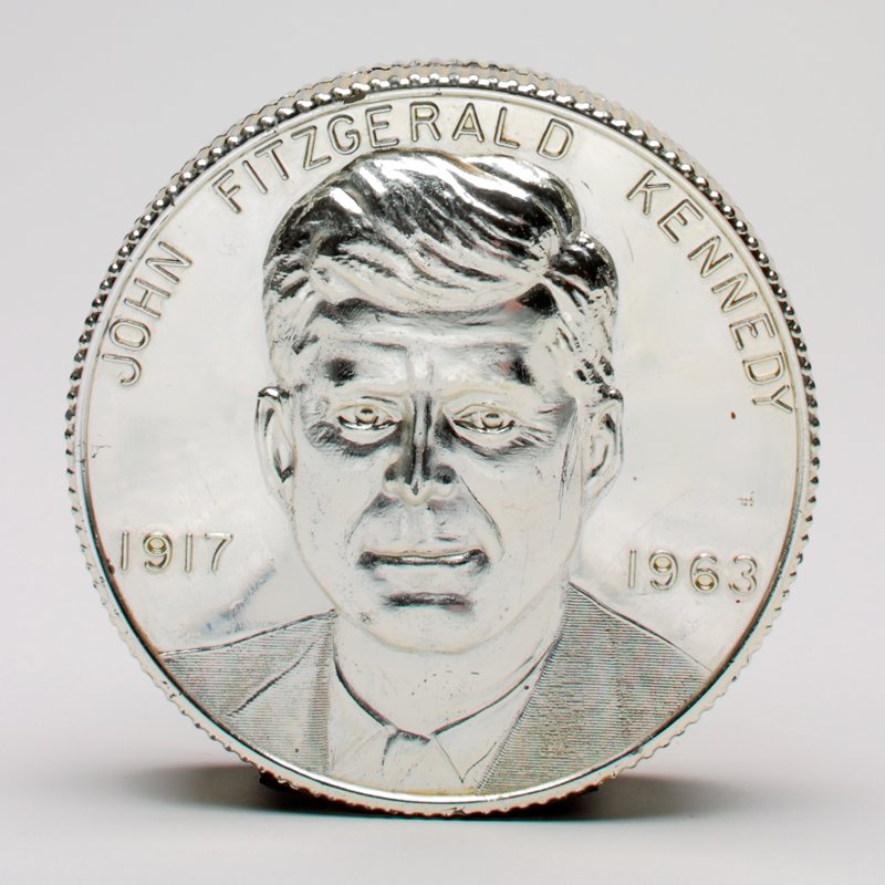 silver colored coin bearin a portrait of JFK with name and dates raised; picture of the eternal flame from his grave on verso with quote; base broken off and lost