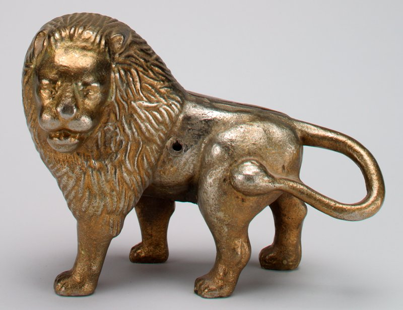 brass plated standing lion with head turned all the way to the left; tail wrapped around to attach at PL side; coin slot atop head; screw replaced by wrong size machine screw; 2 halves attached at side