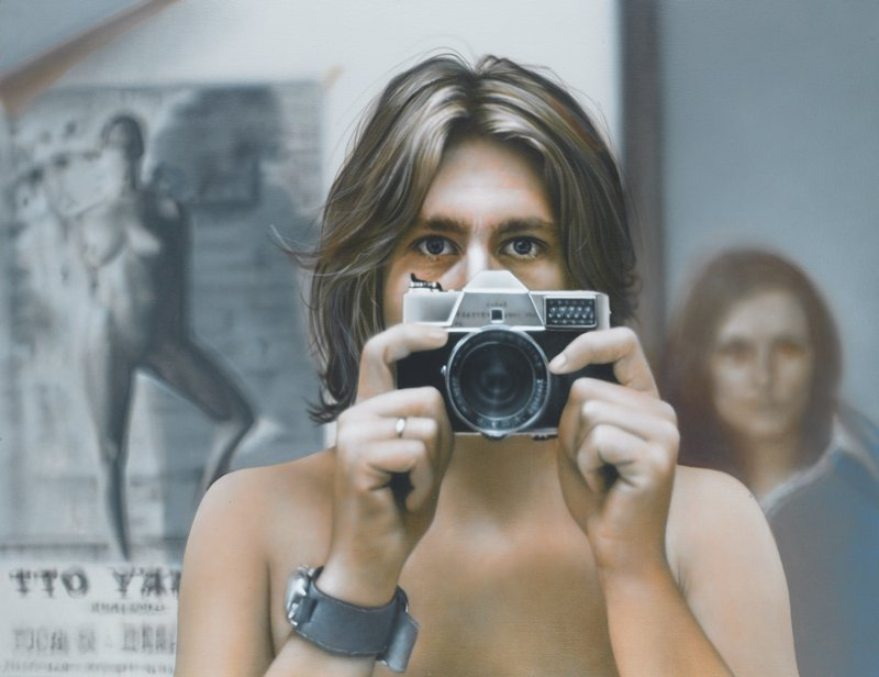 head and shoulders of a man with long hair, wearing a wristwatch and a silver ring and holding a camera below his eyes; black and white nude female image at L; blurry woman's face at R