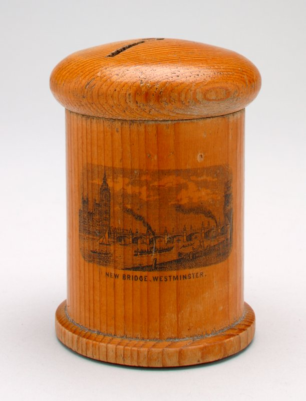 cylindrical wood band, thread spool foot and removable mushroom-shaped top; blank transfer print of the New Bridge, Westminster, at side; coin slot at top