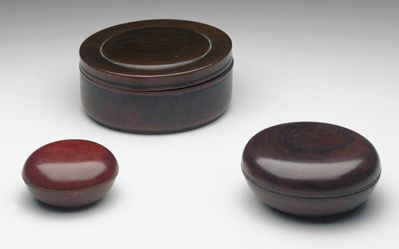 small squat circular covered box; unadorned, thin bead at lower rim of cover and upper rim of body; thin raised base; deep reddish brown in color