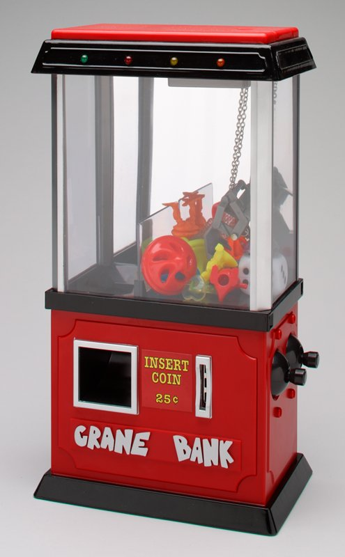 amusement bank; insert coin (25 cents) to operate crane claw for a chance to pick up a prize and drop it down a delivery chute; red base and top; clear body with mirror at back; black accents at foot, waist and top; 4 AA batteries required; 2 controllers at lower right side operate crane