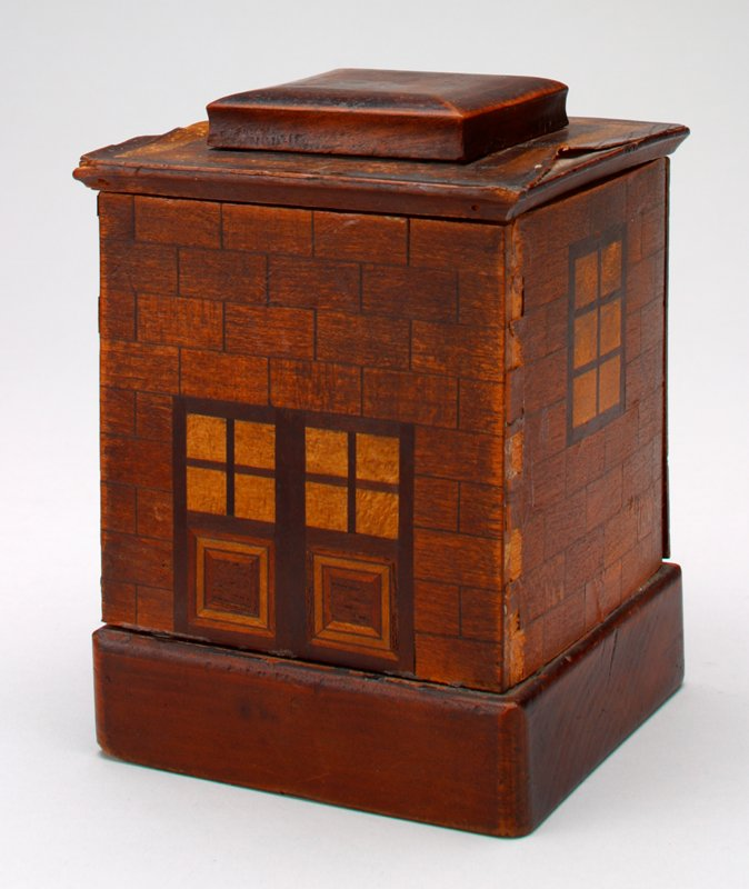 square wood building on wood base with marquetry veneer siding, doors and 2 windows; removable roof with coin slot beneath; sliding rear panel