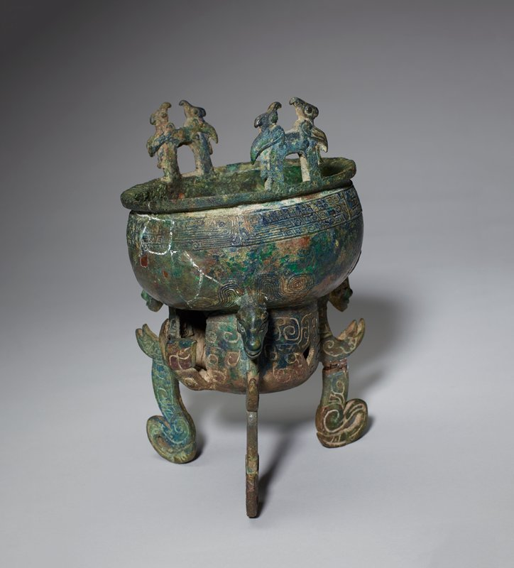 Beneath a broad, shallow bowl is a rounded compartment, possibly for charcoal. The decor in the neck belt is the usual animal triple band violently dissolved antithetical dragons combining to make a t'ao-t'ieh. The bowl is supported by three figures, (demons?) functioning as legs. The heads, much elongated, are human but horned. The bodies display a subtle flow of S-curves from neck to curled-back legs. Three openings in the heating (?) compartment display t'ao-t'ieh figures in incised lines, one of them giving the impression of being detached from the bowl. The upright handles are topped by two confronted birds in the round, their curved beaks raised high. Patina blue-green.