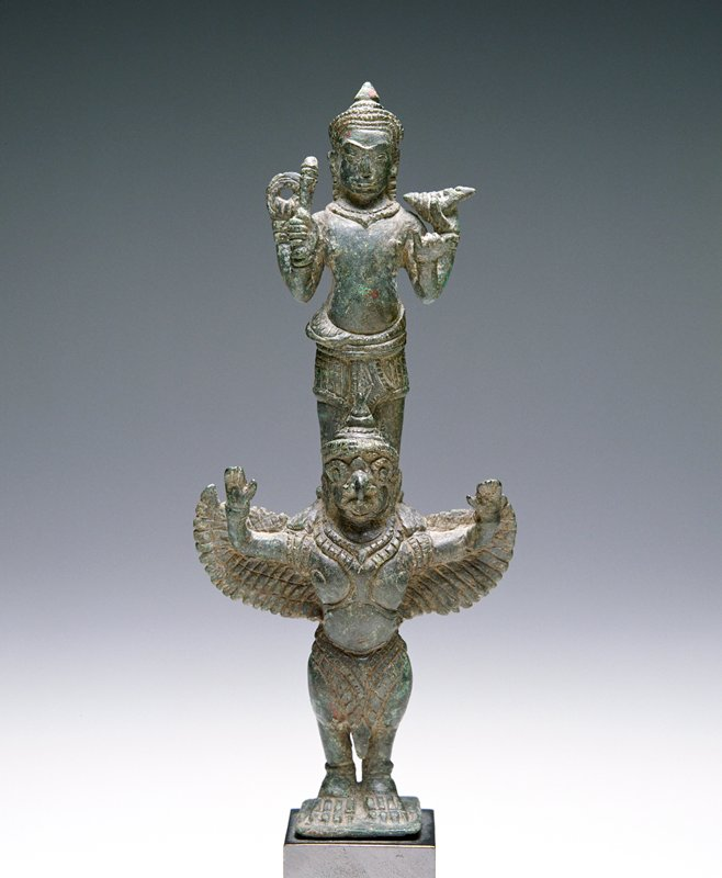 4-armed Vishnu standing on the shoulders of Garuda, with wings, bird's head and bird legs; both have arms raised; attached to mount
