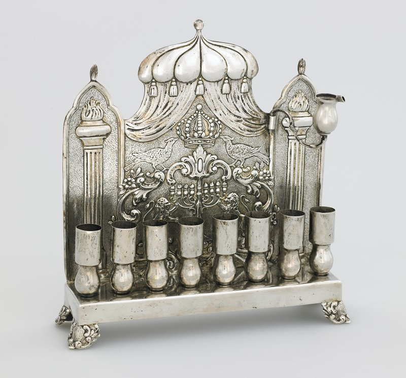 base with 8 cups rests on 4 feet; back has hammered design with rampant lions flanking a menorah topped with a crown flanked by birds; one removable cup on PL side, top