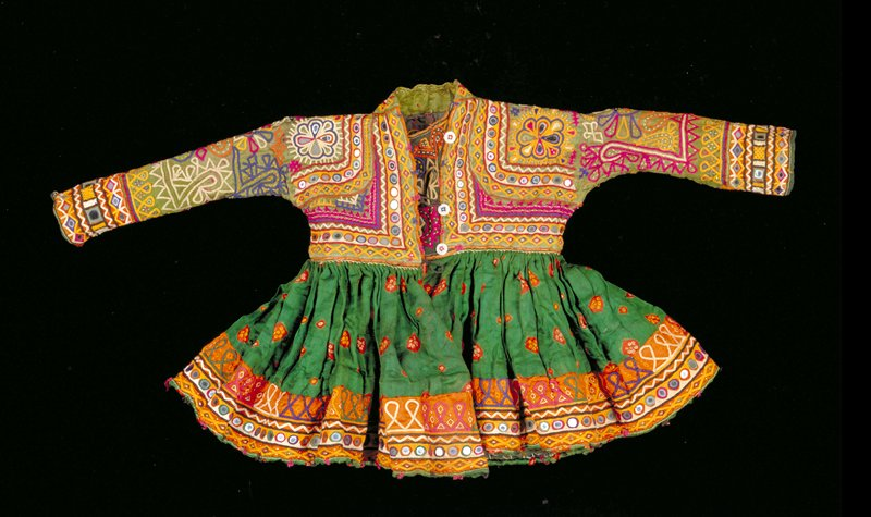 dress with long sleeves; multicolored embroidery and mirrors on green silk bodice; green silk skirt with red, yellow and white tie-dyed flowers; multicolored embroidery and mirrors on orange silk at hem