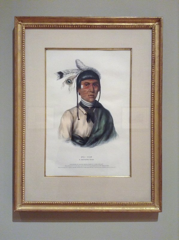 Portrait of Native American man wearing two thin braids, small feathered headdress, tan shirt, green shawl, black bandana, black and white necklace and red lines of pigment on his face