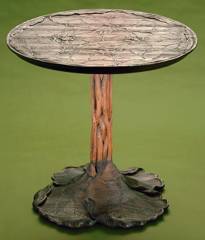 table with untertwining vine support; base of three circular lily pad leaves; top is carved with floral motifs