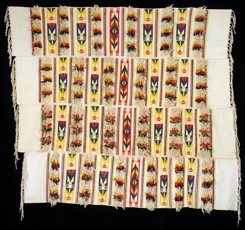 four strips sewn together; white ground with geometric bands in black, red and yellow alternating with loose, wooly fringe in same colors