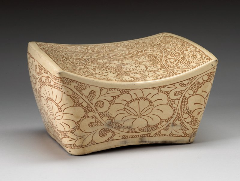 cream-colored glaze on ground; decorated with scroll and floral motifs overall in light brown