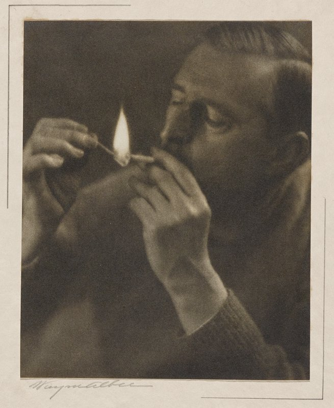 man with slicked-backed hair lighting a cigarette with a match with a large flame