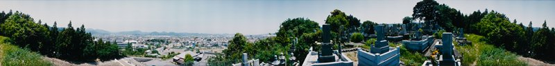422 degree panoramic color photograph; cemetery at right with trees behind; cluster of trees at left; city visible in valley below at left