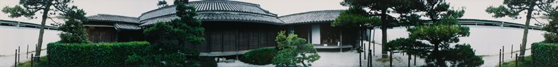 415 degree panoramic color photograph; tile-roofed, traditional Japanese structure at center; modern-looking white structure visible at left and right; trees and shrubs in front of buildings