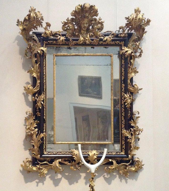 ebony frame with gilt acanthus leaf decoration; central bust of Flora on top crest rail; original mirror panels