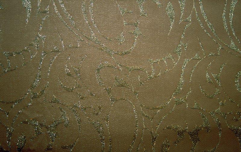 "Jacquard damask with scroll-like design. (See specific pattern descriptions for pattern repeat) Cinnamon & silver. Vert. Rpt. 8""; horiz. Rpt. 4"". Cinnamon"