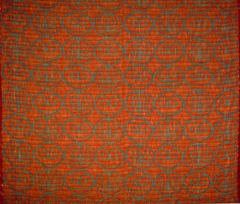 """Warp printed. Scroll pattern. Vert. Rpt. 14.5"""". Authentic warp print with the soft pattern and color modulation of an antique fabric. 7.5"""" circles with 2 African symbols alternating horizontally and vertically. Quilting on circles only. Pieced backing in various colors Red Earth/Indigo"""