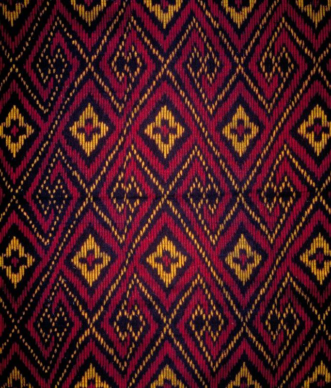 "Handwoven diamond pattern ikat. Vert. Rpt. 15""; horiz. Rpt. 12.5"". Red, black & gold. Night Fire"