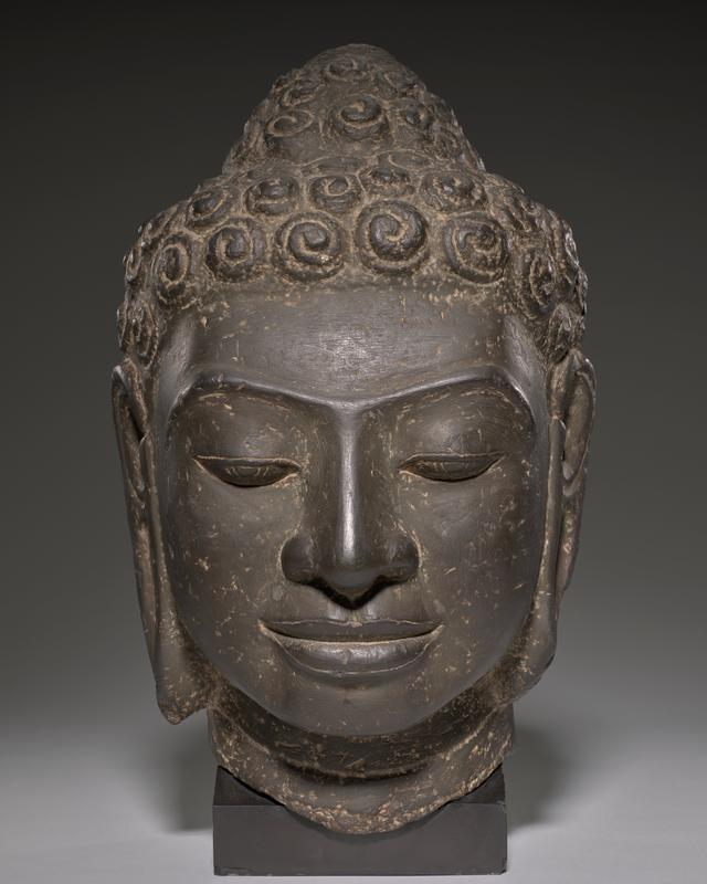 Buddha; traces of gilt on patina; face is square, mouth is wide, nose is flat and hair curls are large - all indicative of the classic style evolved bt the early Dvaravati sculptors